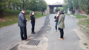 Youth walking with Chief Cook and Lauren Zingarelli of Environment Department observing storm drain