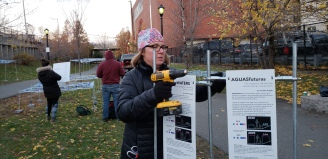 Gretchen Robinkin of Boston Society of Landscape Architects puts up the signs explaining the science behind the art. BSLA has been involved in the work from conception to implementation.
